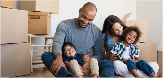 A family of four joyfully sit in their new home with boxes surrounding them.
